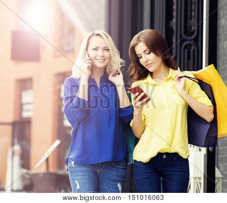 Attractive girls walking in a city center. Women with a shopping bags. Friends spending money. Discount and shopping concept.