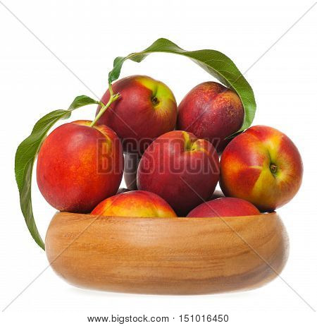 Red nectarines in a wicker basket isolated on white background