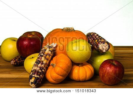 Pumpkingreen and red apples Gourds and corn on a hardwood cutting board
