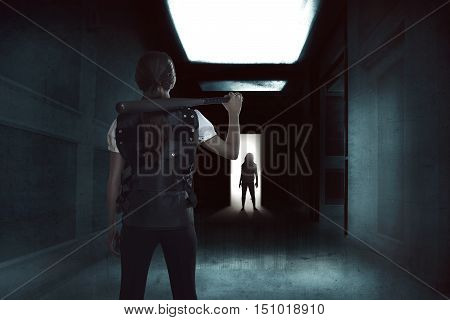 Young woman holding a baseball bat standing in a dark hallway with zombie on the entrance door