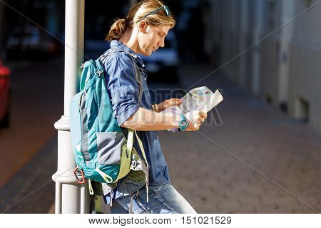 Tourist with backpack in the town holding a map