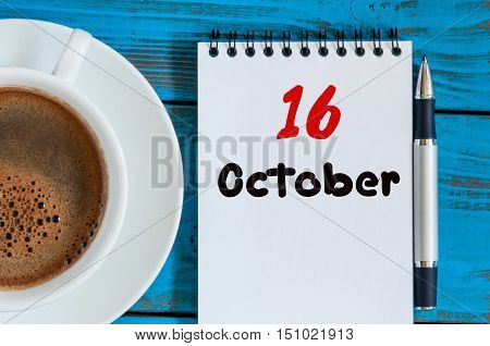 October 16th. Day 16 of month, morning tea cup near calendar on banker workplace background. Autumn time. Empty space for text.