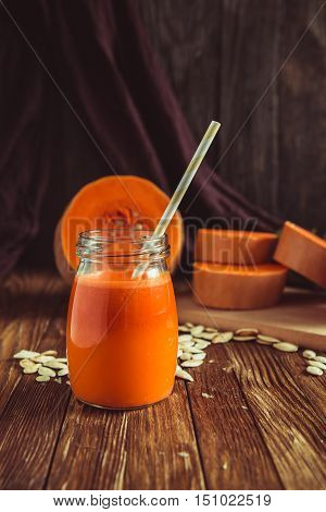 a glass of pumpkin juice placed on a table near the tykv.Novy harvest pumpkins. Pumpkin juice on the table. Autumn harvest of nuts and pumpkins on a table.
