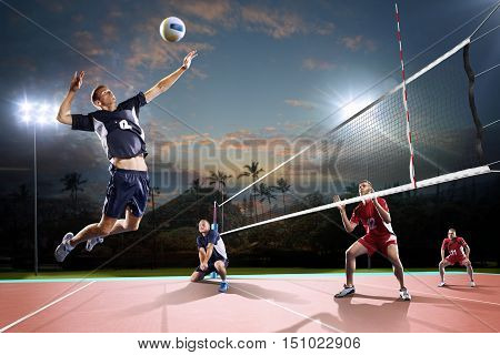 Professional volleyball players in action on the night open air court