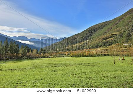 Beautiful mountain landscape with green field and wooden bridge in a sunny day