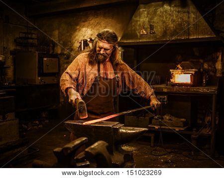 Senior blacksmith forging the molten metal on the anvil in smithy.