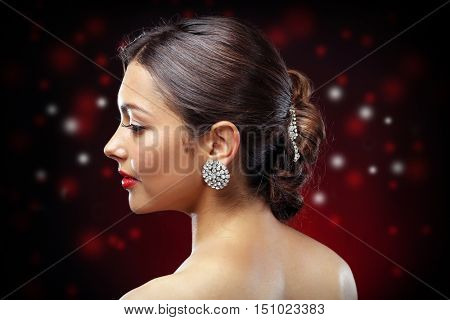 Young beautiful woman with nice hairdo on dark shiny background