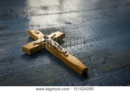 Catholic cross on a wooden background