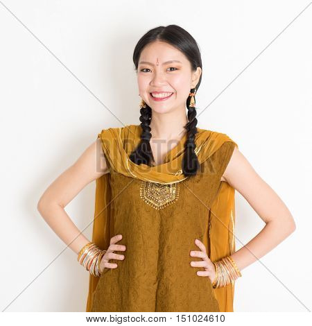 Portrait of beautiful mixed race Indian Chinese woman in traditional Punjabi dress smiling, standing on plain white background.