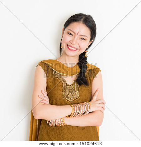 Portrait of arms crossed mixed race Indian Chinese woman in traditional Punjabi dress smiling, standing on plain white background.
