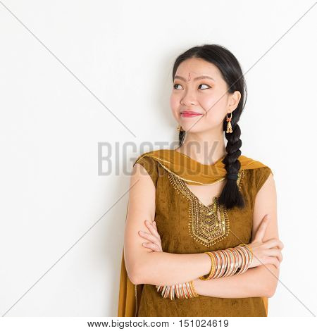 Portrait of arms crossed mixed race Indian Chinese girl in traditional Punjabi dress looking side upward, standing on plain white background.