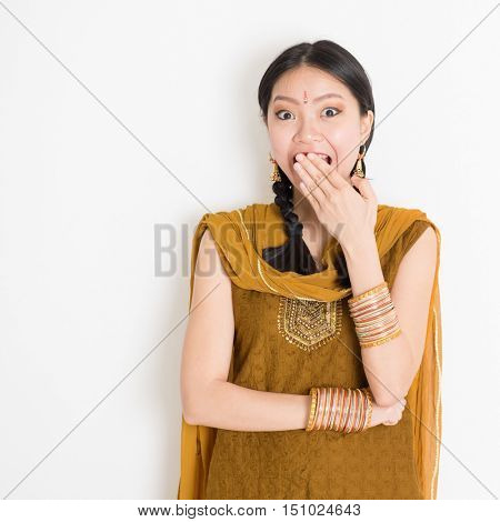 Portrait of shocked mixed race Indian Chinese girl in traditional punjabi dress covering her mouth, surprised emotion, standing on plain white background.