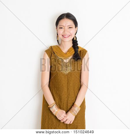 Portrait of young mixed race Indian Chinese woman in traditional Punjabi dress smiling, standing on plain white background.
