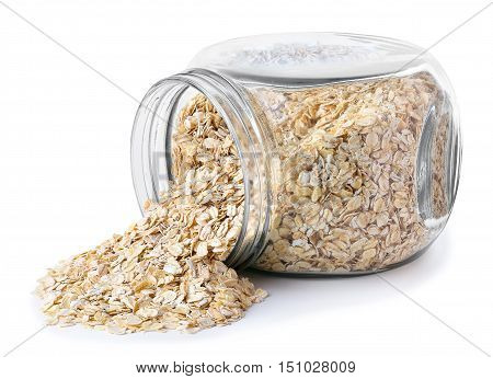 transparent glass jar with rolled oats isolated on white background. Glass jar with oatmeal flakes lying on side isolated on white background. Scattered oatmeal. Dry uncooked oat flakes oatmeal in glass transparent jar