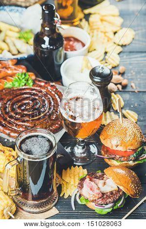 Beer and snack set. Octoberfest food frame concept. Variety of beers, grilled sausages, burgers, fried potato, corn, chips and sauces on dark wooden scorched background. Selective focus