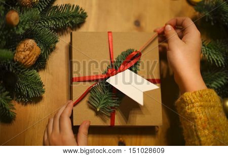 Girl wraping Christmas presents laid on a wooden table background. Cristmas concept