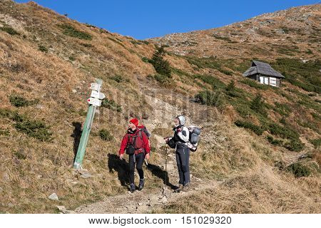 Two Hikers Man and Woman walking on Mountain grassy slope and looking at Trail SIgn Shepherd  Hut and rocky Ridge on Background