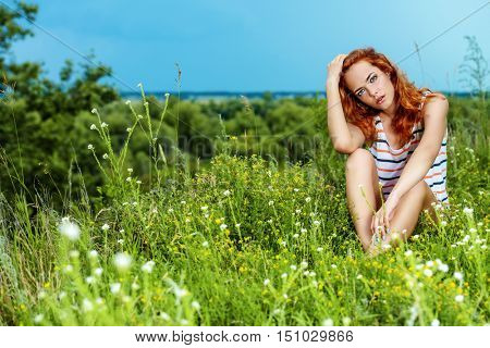 Young girl sitting on a meadow at the cliff. Quiet, slightly anxious mood.