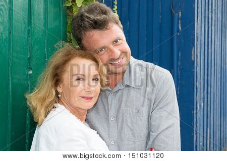Cheerful And Loving Couple With Arms Around