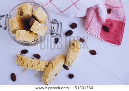 Homemade raisins cookies on white baclground. Jar with freshly baked raisin cookie. Healthy breakfast raisins cookies. Tasty cookies for an afternoon snack. Top view. Copy space.
