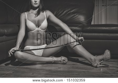 Sexy woman in underwear and whip sit on floor at night black and white bdsm