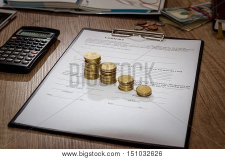 Pen and contract papers calculator coin on wooden desk
