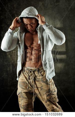 Male bodybuilder posing in hoody in studio.