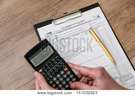 Man filing tax form 1120 with calculator