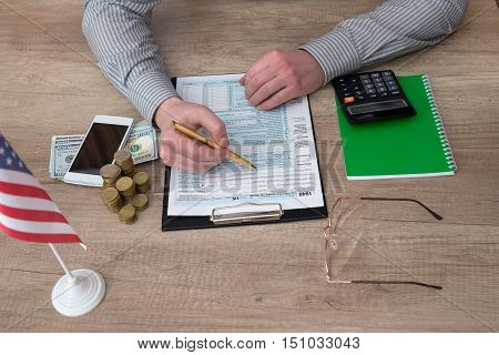 stressed man filling 1040 tax form with mobile, money and calculator
