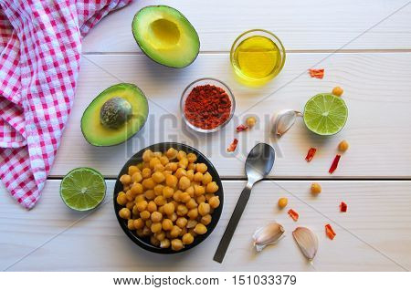Ingredients for cooking delicious Avocado hummus. Chickpeas olive oil lemon juice garlic and spices on wooden background. Healthy eating.