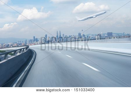 Highway overpass motion blur with city background and aeroplane .