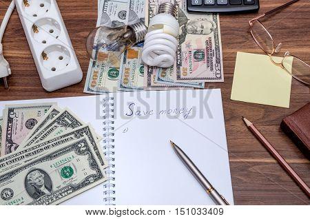Energy saving light bulb and dollar bills
