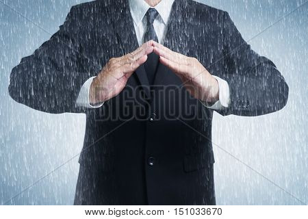 Businessman in suit with two hands in position to protect in rainy weather day (focus on hand blur out the suit). It indicates many aspects such as car insurance coverage support assurance reliability.