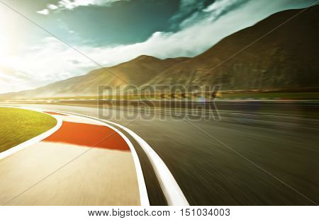 Motion blurred racetrack with mountain background warm mood