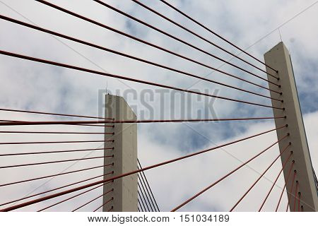 Suspension bridge pillar and cables from below in  horizontal 3:2 format.