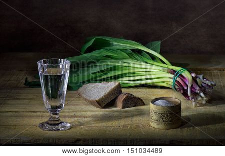 Wild onion, black bread and vodka in glass