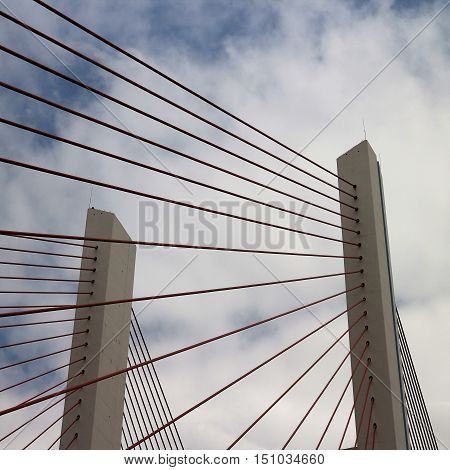 Suspension bridge pillar and cables from below in  square format.