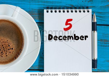 December 5th. Day 5 of month, calendar on freelancer workplace background with coffee cup. Top view. Winter time. Empty space for text.