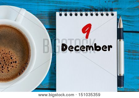 December 9th. Day 9 of month, calendar on freelancer workplace background with coffee cup. Top view. Winter time. Empty space for text.
