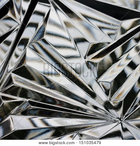 Geometric shapes pattern in cut glass in square format.