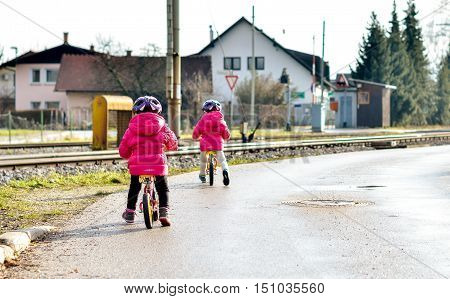 Twins children riding balance bikes on the road with helmet. Young toddlers with pink jackets and purple bicycle helmet are riding balance bikes in the winter on the road with railroad tracks near by