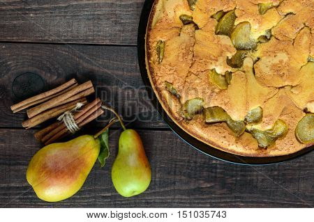 Home baked biscuit flavored pear charlotte cake with cinnamon. On a dark wooden background. The top view.