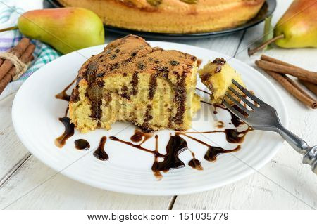 A piece of home baked biscuit flavored pear charlotte cake with cinnamon and chocolate syrup. On a white plate on a light wooden background.