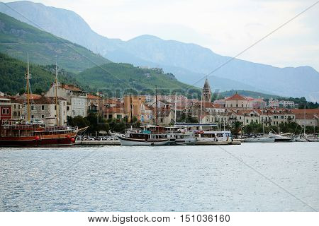 Picturesque old town with medieval architecture and harbor pier with yachts boats on sea coast on mountain landscape