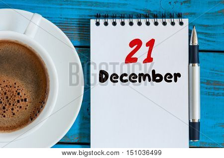 December 21st. Day 21 of month, calendar on workplace background with morning coffee cup. Top view. Winter time. Empty space for text.