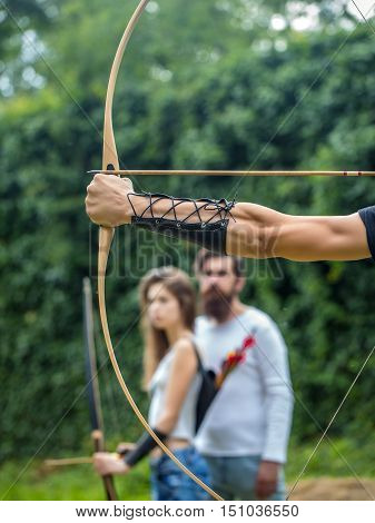 Bow shooting lesson for the attractive couple. Bearded handsome man and attractive girl learn new hobby