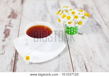 Chamomile tea in a mug at wooden floor. Herbal natural healthful drink