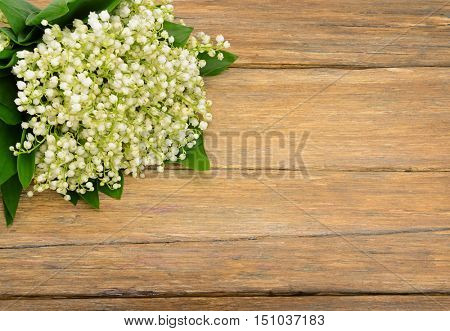 Bouquet lily of the valley on wooden table. Spring flowers on old wooden background. Top view. Copy Space for your text.