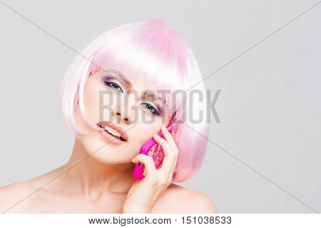sexy glamour girl or woman with fashionable makeup on pretty face and short hairstyle or pink wig holding plastic toy mobile phone in studio on light background