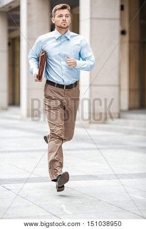Young businessman with a briefcase running in a city street. Hurrying to work.